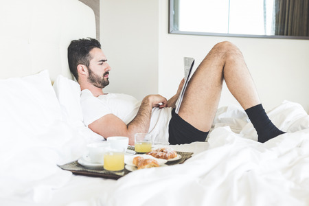 breakfast in bed: A man is reading a newspaper lying on the bed while is waiting for his wife to have breakfast together. On the bad there is a try with coffees, juices and croissants. Stock Photo