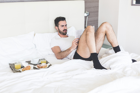 coffees: A man is reading a newspaper lying on the bed while is waiting for his wife to have breakfast together. On the bad there is a try with coffees, juices and croissants. Stock Photo