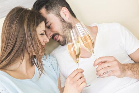 Gelukkig paar het maken van een toast op het bed. Het zou kunnen zijn op Valentijnsdag of verjaardag, ze zijn elkaar kijken en lachen. Setting kon luxe huis of hotel kamer zijn.