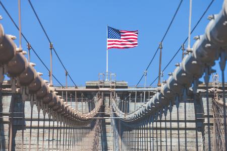 bandera estados unidos: Estados Unidos Bandera en la parte superior del puente de Brooklyn. Hay un cielo azul profundo en el fondo, en primer plano están todos los cables del puente. Concepto de patriotismo.