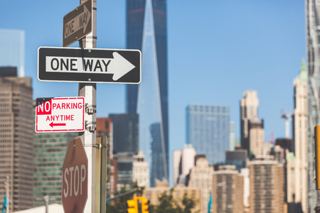 one way sign: One way road sign in New York, with modern skyscrapers on background. Main background colors are gray and blue.