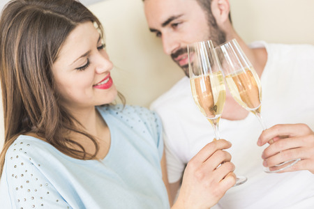 Happy couple making a toast on the bed. It could be on Valentine's day or for birthday, they're looking each other and smiling. Setting could be luxury home or hotel bedroom. photo