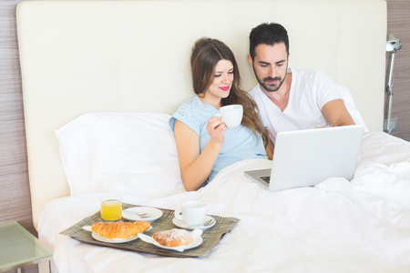 breakfast in bed: A man and a woman are having breakfast on the bed. They are drinking coffee and juice and eating croissants. They are enjoying relax on holiday but they are also working with computer. Stock Photo