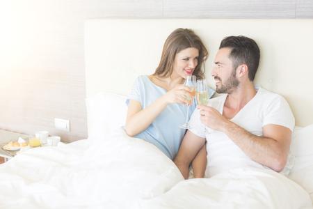 jovenes enamorados: Pareja feliz haciendo un brindis en la cama. Podr�a ser en el d�a de San Valent�n o para el cumplea�os, que est�n buscando el uno al otro y sonriendo. Ajuste podr�a ser la casa de lujo o habitaci�n de hotel.