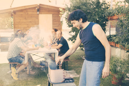 late twenties: Man cooking meat on the barbecue. He, and the friends of him on background, are all on late twenties. They are eating outdoor on the grass. Everybody is wearing summer clothes. Stock Photo