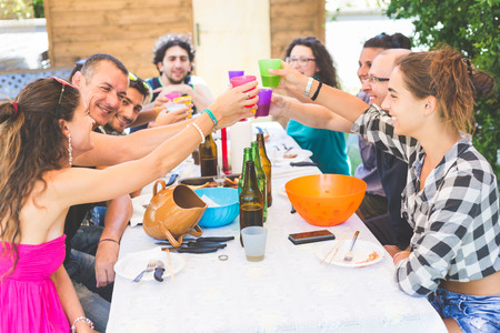 family and friends: A group of people sitting on the table having lunch. A multicultural group of friends is toasting while they are eating. They are having fun together. Everybody is wearing summer clothes. Stock Photo