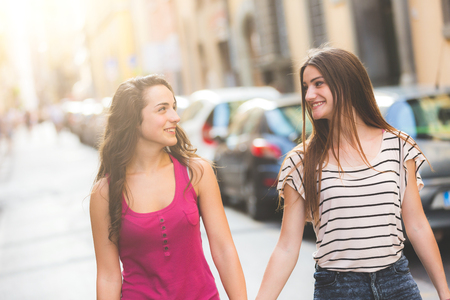 Two girls walking on the street. They are two young girls walking together and  holding their hands. They are wearing summer clothes and they are happy.