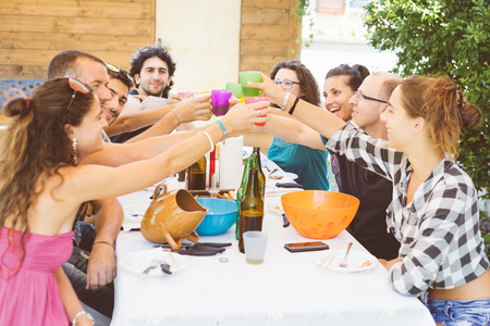 food and drinks: A group of people sitting on the table having lunch. A multicultural group of friends is toasting while they are eating. They are having fun together. Everybody is wearing summer clothes. Stock Photo