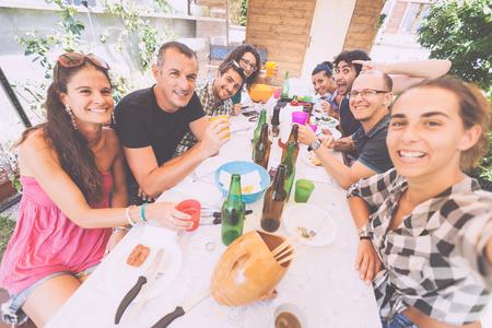 Groep van mensen die selfie terwijl lunchen buiten. Een multiculturele groep vrienden neemt een selfie tijdens het eten. Ze zijn blij en er zijn een heleboel borden en flessen op de tafel.