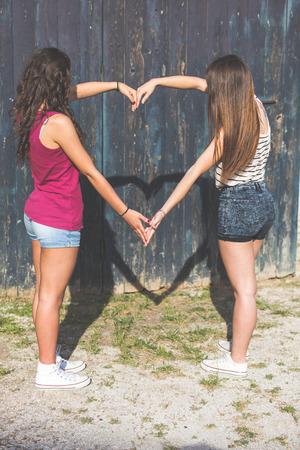 lesbienne: Couple de filles faisant une ombre en forme de coeur avec les bras. Ils sont deux jeunes filles portant des vêtements d'été en plein air. Ils se joignent à leurs bras dessinant un coeur sur un fond de bois. Banque d'images