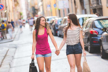 lesbian love: Two girls walking on the street. They are two young girls walking together and  holding their hands. They are wearing summer clothes and they are happy.