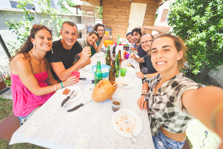 party table: Group of people taking selfie while having lunch outdoor. A multicultural group of friends is taking a selfie while eating. They are happy and there are a lot of plates and bottles on the table.