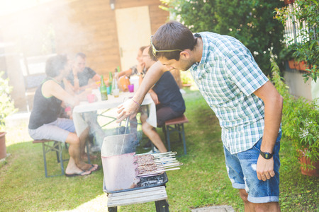 barbecue fire: Man cooking meat on the barbecue. He, and the friends of him on background, are all on late twenties. They are eating outdoor on the grass. Everybody is wearing summer clothes. Stock Photo