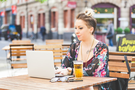 laptop outside: Girl working on her computer outdoor. She is writing on the keyboard while sitting at open air. There are a beer, a smart phone and a pair of glasses on the table. Stock Photo