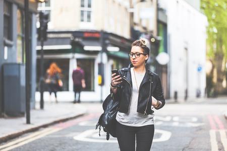 persona caminando: Chica caminando por la calle con su teléfono. Una mujer camina sola en Londres. Ella está mirando a su teléfono inteligente. Borrosa en el fondo hay casas y tiendas típicas inglesas. Foto de archivo