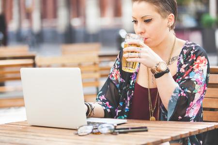 tomando alcohol: Muchacha que trabaja en su computadora al aire libre y beber una pinta de cerveza. Ella est� escribiendo en el teclado mientras se est� sentado en el aire libre. Hay un tel�fono inteligente y un par de vasos en la mesa. Foto de archivo