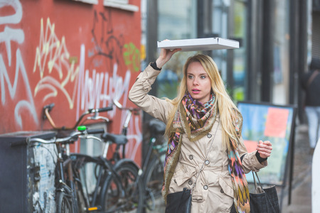 woman scarf: Woman with a pizza in Copenhagen. A blond woman is walking down the street. She is using a pizza to shelter from the rain. She is wearing a raincoat and a colourful scarf.