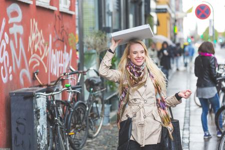 personas en la calle: Mujer con una pizza en Copenhague. Una mujer rubia está caminando por la calle. Ella está usando una pizza para protegerse de la lluvia. Ella lleva un impermeable y una bufanda colorida.