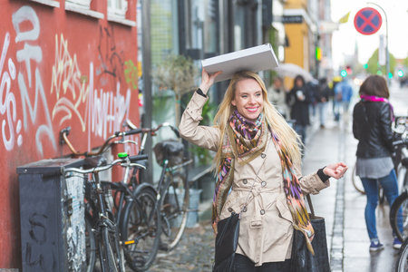 street people: Woman with a pizza in Copenhagen. A blond woman is walking down the street. She is using a pizza to shelter from the rain. She is wearing a raincoat and a colourful scarf.