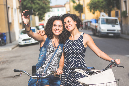urban street: Female friends taking a selfie with their bicycles in the city. They are two women, a couple or sisters, wearing summer clothes and looking at their smart phone. There are some houses on background. Stock Photo