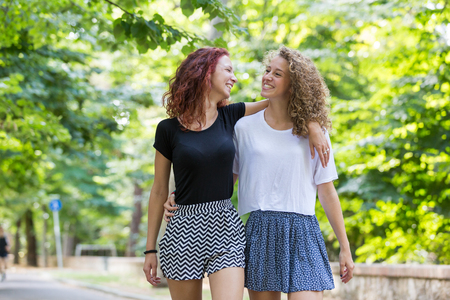 lesbian girls: Two girls walking embraced at park. . They are two young girls walking embraced and  smiling to each other. They are having fun together on a summer day.
