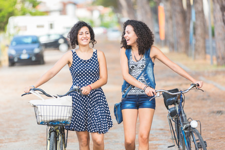 Female friends, a couple or sisters,  holding bikes and walking in the city. They are two women, they are talking and smiling, and wearing summer clothes. There are some trees on the background. photo