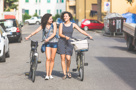 Female friends, a couple or sisters,  holding bikes and walking in the city. They are two women, they are talking and smiling. There are some houses and cars on background. photo