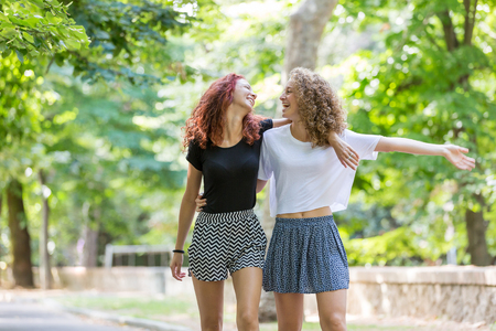 gay girl: Two girls walking embraced at park. . They are two young girls walking embraced and  smiling to each other. They are having fun together on a summer day.