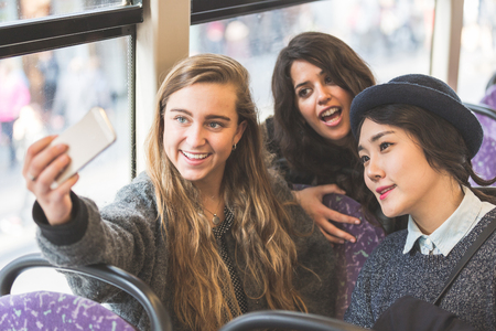 buss: Three womentaking a selfie in the buss. They are a mixed group with a caucasian, an asian and a spanish woman. They are friends and they are travelling together by bus.