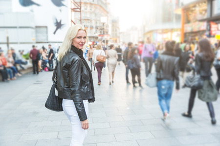 Beautiful woman walking in crowded London street at sunset. She is a blonde woman on her early forties. Backlight shot with blurred people on background.