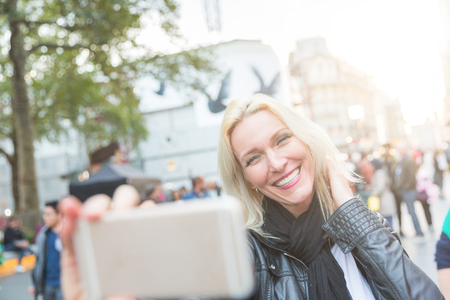 early forties: Beautiful adult woman taking a selfie in London at sunset. She is a blonde woman on her early forties, she looks candid and spontaneous. Backlight shot with blurred people on background.