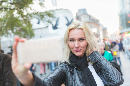 Beautiful adult woman taking a selfie in London at sunset. She is a blonde woman on her early forties, she looks candid and spontaneous. Backlight shot with blurred people on background.
