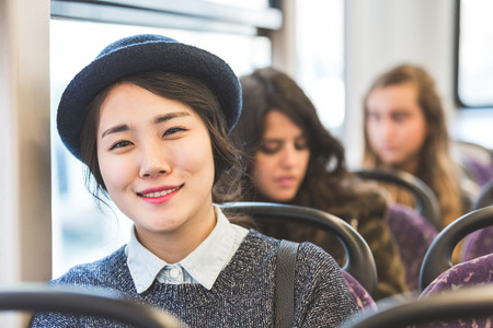 Portrait of an asian woman on a bus, with other people on background. She is wearing a hat and looking at camera smiling. Transportation and travel theme.