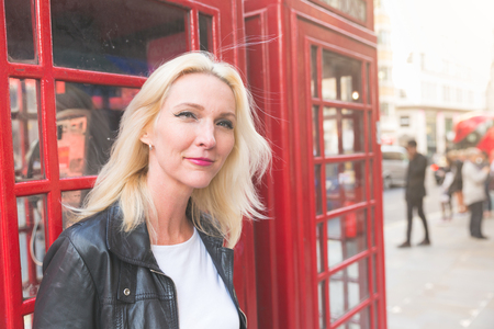 Beautiful woman portrait in London with red phone booth. She is a blonde woman on her early forties, she looks candid and spontaneous, looking in camera with a natural smile.