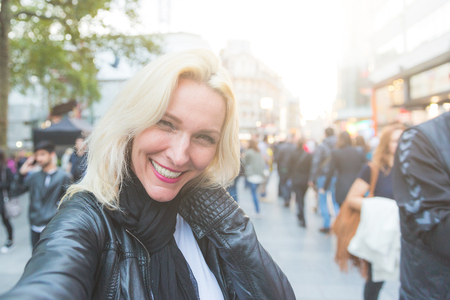 early forties: Beautiful adult woman taking a selfie in London at sunset. She is a blonde woman on her early forties. Backlight shot with blurred people on background. Camera point of view.