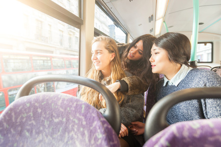 spanish woman: Three women looking out the window from. the bus. They are a mixed group with a caucasian, an asian and a spanish woman. They are friends and they are travelling together by bus. Stock Photo