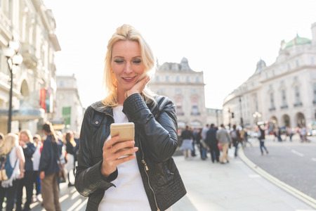 early forties: Adult woman looking at smart phone in London at sunset. She is a blonde woman on her early forties, she looks candid and spontaneous. Backlight shot with blurred people on background. Stock Photo