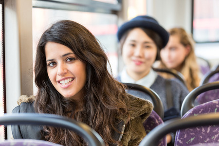 spanish: Portrait of a spanish woman on a bus, with other people on background. She has long black hair and a candid smile. Transportation and travel theme. Stock Photo
