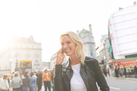 Adult woman talking on the phone in London at sunset. She is a blonde woman on her early forties, she looks candid and spontaneous. Backlight shot with blurred people on background.