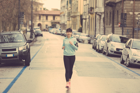 winter road: Beautiful young woman jogging alone in a city street. There is no traffic, early morning and cloudy day. She wears light blue sweatshirt, black leggings and pink shoes. Wearable technology theme.