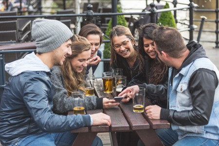 Group of friends enjoying a beer at pub in London and looking at a smart phone,  laughing and looking each other. They are four girls and two boys in their twenties.