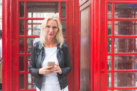 cabina telefonica: Retrato de la mujer hermosa en Londres con cabina de tel�fono rojo. Ella es una mujer rubia en sus cuarenta y pocos a�os, ella se ve sincero y espont�neo, mirando en la c�mara y la celebraci�n de un tel�fono inteligente. Foto de archivo