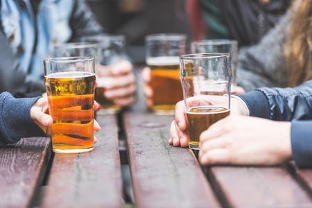 hombre tomando cerveza: Manos que sostienen los vidrios con la cerveza en una mesa en el pub de Londres. Un grupo de amigos está disfrutando de tiempo de la cerveza en la ciudad, cerca de las gafas. Foto de archivo