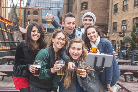 Group of friends taking a selfie with the stick while enjoying a beer at pub in London, toasting and laughing. They are four girls and two boys in their twenties.