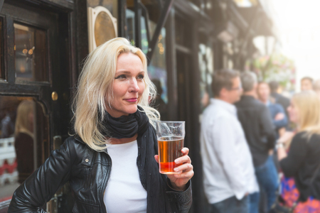 Beautiful woman enjoying a pint of beer in London. She is a blonde woman on her early forties, she looks candid and spontaneous, holding a glass of beer outside the pub.