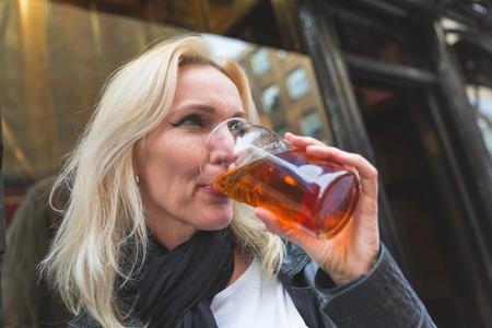 Schöne Frau genießen ein Bier in London. Sie ist eine blonde Frau auf Anfang vierzig, sie sieht aus offenen und spontan, mit einem Glas Bier vor dem Pub.