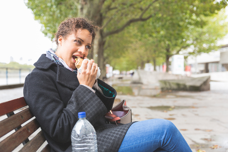 people   lifestyle: Young woman having lunch in London. She is sitting on a bench, eating a sandwich, typical lunch for many workers in the city. Urban lifestyle concept.
