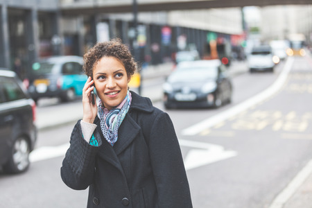 Young woman talking on the phone next to a busy street in London. She is a beautiful mixed race woman on her late twenties. Lifestyle and communications concepts in a urban context. Stock Photo
