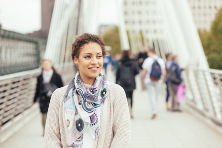 looking away from camera: Young mixed race woman walking on a bridge in London. She is smiling and looking away from camera. There are some blurred persons on background. Tourism and lifestyle concepts. Stock Photo