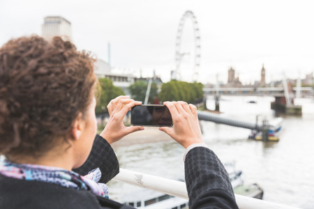 late twenties: Young woman taking photo of Big Ben in London with her smart phone. She is a mixed race woman on her late twenties, with light dark skin and curly hair. Tourism and lifestyle concepts
